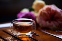 Thé frais dans la tasse en verre au-dessus du fond en bois de table Photos stock