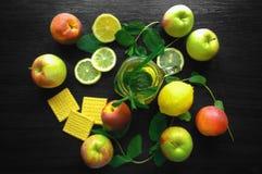 Thé frais naturel dans une tasse sur la table en bois avec le citron et les pommes Image libre de droits