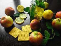Thé frais naturel dans une tasse sur la table en bois avec le citron et les pommes Images stock