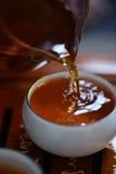 Thé frais se renversant de la cruche en verre dans la tasse en céramique blanche Photos libres de droits