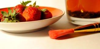 Thé, fraise et brosse dessus photographie stock libre de droits