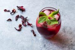 Thé froid de ketmie d'infusion avec de la glace et les feuilles en bon état photographie stock libre de droits