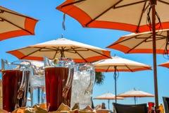 Thé glacé et eau glacée pour le rafraîchissement de la chaleur d'été sous les parasols Photo libre de droits