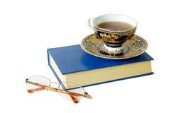 Thé, livre et verres Photos stock