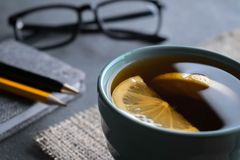 Thé noir avec des tranches de citron sur une serviette de toile de jute avec le stylo de bloc-notes, un crayon et des verres images stock