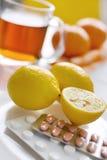 Thé noir avec les citrons et les pilules frais de grippe dans la boursouflure avec thermo image stock