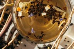 Thé noir avec les fleurs bleues, la peau d'orange et les pétales dans un transpa Photo stock