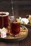 Thé noir, bonbons orientaux, dates et écrous sur un dos en bois foncé Image stock