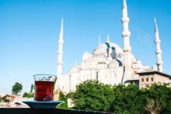 Thé noir turc aromatique traditionnel dans un verre en forme de tulipe À l'arrière-plan, la mosquée bleue s'appelle également images stock