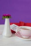 Thé noir, vase à fleur et carte heureuse de jour de mères sur la surface en bois Photographie stock libre de droits
