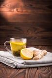 Thé organique vert Une tasse de thé sur un fond en bois foncé Une tasse en verre a rempli de liquide, de feuilles de thé vertes n Photo stock