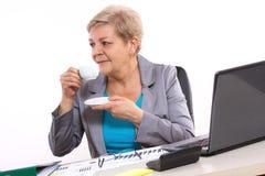 Thé ou café potable plus âgé de femme d'affaires au bureau dans le bureau, coupure au travail Photos libres de droits