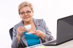 Thé ou café potable plus âgé de femme d'affaires au bureau dans le bureau, coupure au travail Photo stock