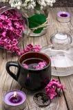 Thé parfumé et une branche de lilas Images libres de droits