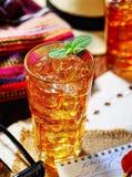 Thé parfumé froid dans un verre sur la serviette originale, feuilles en bon état Photographie stock