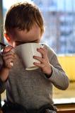 Thé potable d'enfant mignon photos libres de droits
