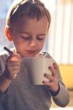 Thé potable d'enfant mignon photographie stock