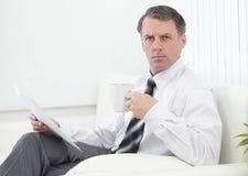 Thé potable d'homme d'affaires sûr et lecture d'un document, se reposant dans une chaise dans la chambre d'hôtel Image libre de droits