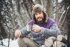 Thé potable d'homme barbu dans la forêt photographie stock libre de droits
