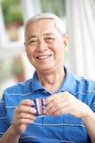 Thé potable d'homme chinois aîné sur le sofa à la maison Image stock