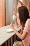 Thé potable de belle femme et regard à l'extérieur photos stock