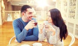 Thé potable de couples heureux au café Photographie stock libre de droits
