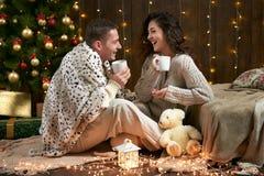 Thé potable de couples heureux et parler dans la décoration de Noël, se reposant sur le plancher dans l'intérieur en bois foncé a Photo libre de droits