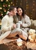 Thé potable de couples heureux et parler dans la décoration de Noël, se reposant sur le plancher dans l'intérieur en bois foncé a Images libres de droits