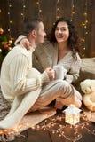 Thé potable de couples heureux et parler dans la décoration de Noël, se reposant sur le plancher dans l'intérieur en bois foncé a Image libre de droits