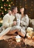 Thé potable de couples heureux et parler dans la décoration de Noël, se reposant sur le plancher dans l'intérieur en bois foncé a Photographie stock libre de droits