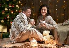 Thé potable de couples heureux et parler dans la décoration de Noël, se reposant sur le plancher dans l'intérieur en bois foncé a Photo stock