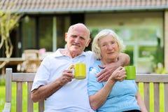 Thé potable de couples supérieurs affectueux dans le jardin Photo libre de droits