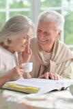 Thé potable de couples supérieurs avec le livre Image libre de droits