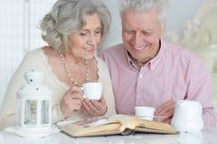 Thé potable de couples supérieurs avec le livre Image stock