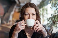 Thé potable de femme attirante à la pause de midi de la tasse blanche et du sourire photo stock
