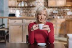Thé potable de femme calme attentive à la maison Photographie stock