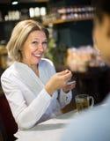 Thé potable de femme et parler dans le café Photo stock