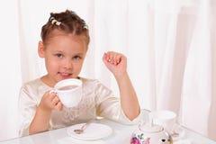 Thé potable de fille assez petite Photos libres de droits