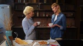 Thé potable de gentille femme avec plaisir avec sa mère pluse âgé banque de vidéos
