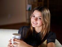 Thé potable de jeune fille à la maison images stock