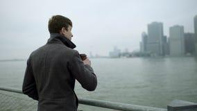 Thé potable de jeune homme et vue de apprécier sur Manhattan près du fleuve Hudson banque de vidéos