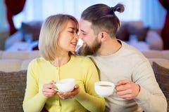 Thé potable de jeunes couples affectueux dans le restaurant Images stock