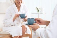 Thé potable de jeunes couples romantiques dans le salon de station thermale images stock