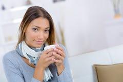 Thé potable de sourire de femme caucasienne de portrait d'intérieur photos libres de droits