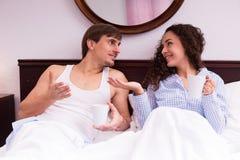 Thé potable de type et de fille et causerie dans le lit Photographie stock