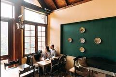 Thé potable de type et de fille dans un café image stock