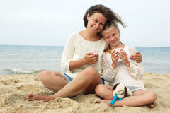 Thé potable heureux de parent et d'enfant sur la plage Photo stock