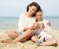 Thé potable heureux de parent et d'enfant sur la plage Images stock