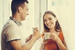 Thé potable ou café de jeunes couples à la maison Image stock