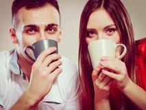 Thé potable ou café de jeunes couples drôles Images libres de droits